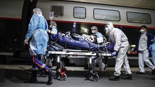 Des soignants prennent en charge un patient atteint du Covid-19, le 1er avril 2020 à la gare d'Austerlitz, à Paris, pour l'embarquer à bord d'un TGV vers la Bretagne. (THOMAS SAMSON / AFP)