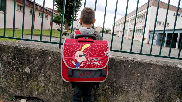 Un enfant devant une cour de récréation. (JULIO PELAEZ / MAXPPP)