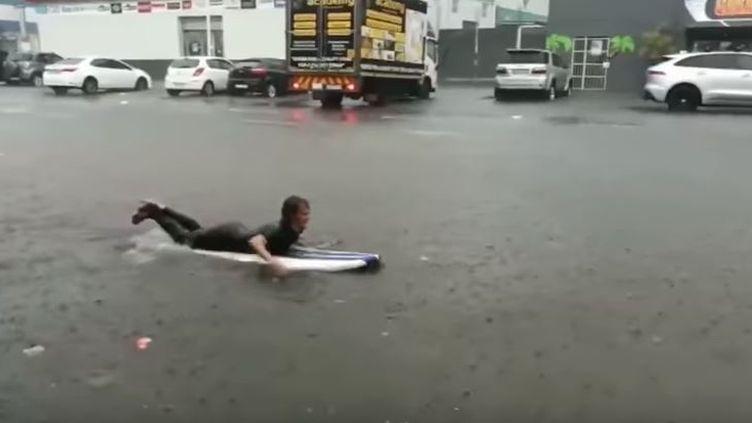 "Capture écran de la vidéo Youtube ""Surfer takes to the flooded streets of Durban"", jeudi 12 octobre 2017. (MIKE FREW/YOUTUBE)"