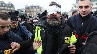 Jérôme Rodrigues, blessé à l'œil lors de heurts avec les forces de l'ordre, est escorté par des sapeurs-pompiers, le 26 janvier 2019 à Paris. (ZAKARIA ABDELKAFI / AFP)