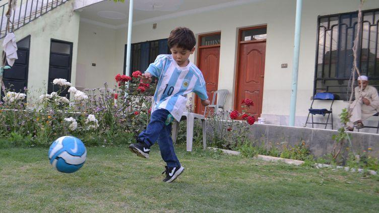 Murtaza, un petit Afghan de 5 ans, joue avec son maillot dédicacé par Lionel Messi, le 3 mai 2016, à Quetta(Pakistan). (MAZHAR CHANDIO / AFP)