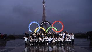 Des personnes posent devant des anneaux olympiques géants sur l'esplanade du Trocadéro, près de la Tour Eiffel, le 13 septembre 2017 à Paris. (CHRISTOPHE SIMON / AFP)
