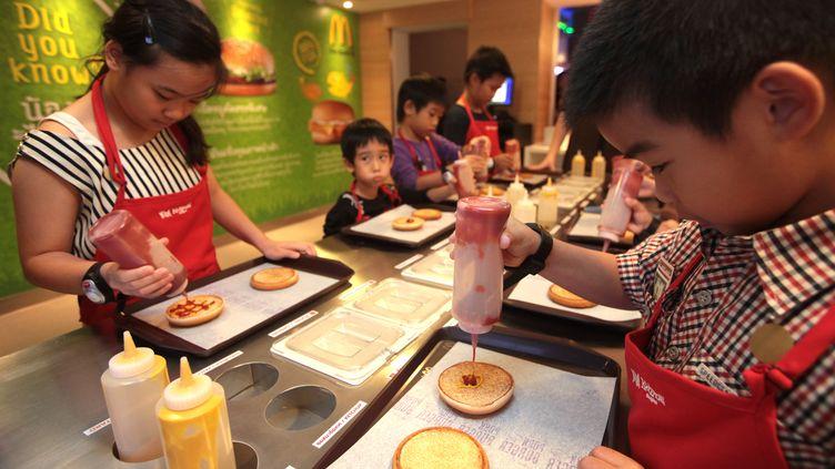 Des enfants préparent des hamburgers au McDonald's du parc d'attractions Kidzania, à Bangkok (Thaïlande), le 4 avril 2013. (PATIPAT JANTHONG / BANGKOK POST / AFP)