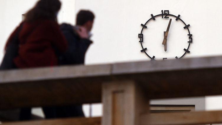 Des passants jettent un coup d'oeil à l'horloge de la mairie de Biarritz, quelques minutes après le couvre-feu, le 16 janvier 2021. (GAIZKA IROZ / AFP)
