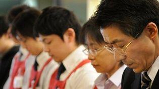 Des salariés d'un commerce de Tokyo observent une minute de silence un mois après le séisme du 11 mars au Japon (AFP / Trou Yamanaka)