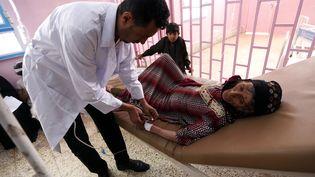 Un médecin examine une femme potentiellement atteinte du choléra, le 12 août 2017 à Sanaa (Yémen). (MOHAMMED HUWAIS / AFP)