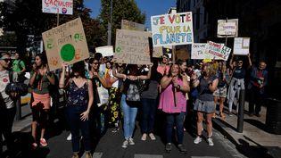 Des manifestants tiennent des pancartes lors de la marche pour le climat, le 13 octobre 2018 à Marseille. (GERARD JULIEN / AFP)