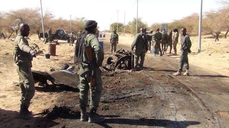 Des soldats maliens observent la scène après une attaque suicide menée par un jihadiste près de l'aéroport de Tombouctou au mali, le 21 avril 2013. (SIPA)