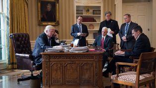Donald Trump au téléphone avec Vladimir Poutine, devant ses conseillers, dans le bureau ovale, à la Maison Blanche, le 28 janvier 2017. (GETTY IMAGES)