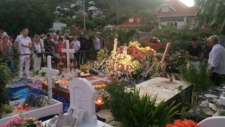 Les fans se recueillent sur la tombe de Johnny Hallyday au cimetière de Lorient à Saint-Barthélémy, le 5 décembre 2018. Un autre caveau est en projet à l'initiative de Laeticia Hallyday. (VALENTINE AUTRUFFE / AFP)