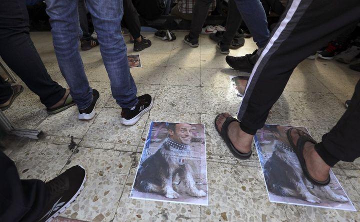Des photomontages, montrant le visage d'Emmanuel Macron sur le corps d'un chien, piétinés à Ramallah, en Cisjordanie, le 30 octobre 2020. (ABBAS MOMANI / AFP)