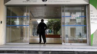Une personne entre, le 16 ocotbre 2012 à Paris, au siège social des organismes de retraite complémentaire Agirc et Arrco. (KENZO TRIBOUILLARD / AFP)