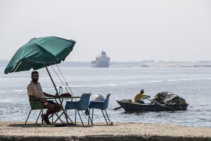 Un pêcheur au bord du canal de Suez... Au loin un cargo poursuit son voyage. (KHALED DESOUKI / AFP)
