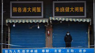 Un garde devant une boutique, à Hubei, dans le Wuhan, en Chine, le 24 janvier 2020. (HECTOR RETAMAL / AFP)