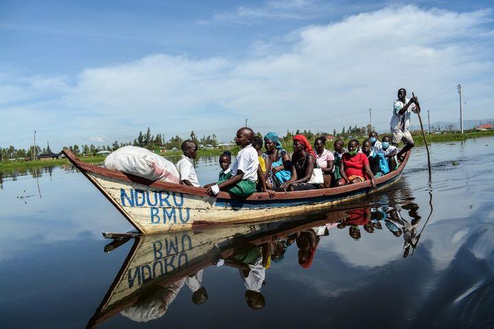 Enfants et parents du district de Nyando en pirogue sur le lac Victoria pour se rendre à l'école, le 4 janvier 2021. (BRIAN ONGORO / AFP)