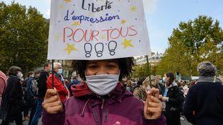 """Une jeune fille tient une pancarte """"Liberté d'expression pour tous"""" lors d'un reassemblement place de la République à Paris,en hommage à Samuel Paty, le 18 octobre 2020. (LAURENCE KOURCIA / HANS LUCAS / AFP)"""