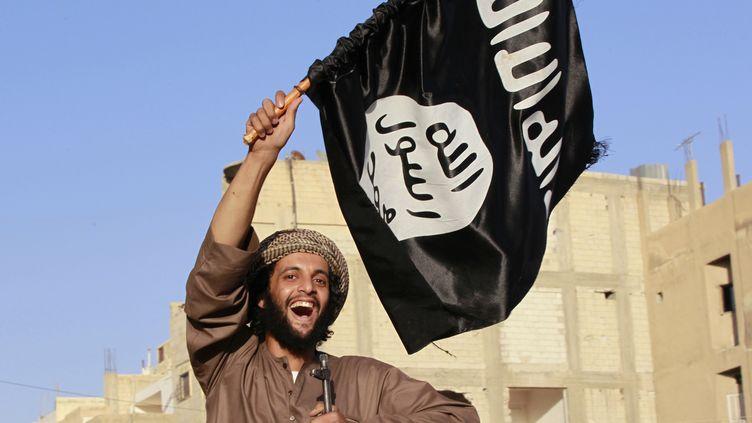 Un combattant de l'organisation Etat islamique brandit un drapeau à Raqqa (Syrie), le 30 juin 2014. (REUTERS)