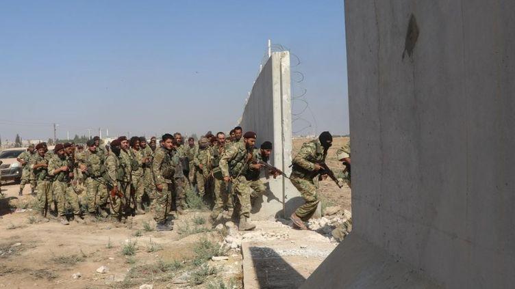 Des membres de l'Armée nationale syrienne, alliée de la Turquie, entrent sur le territoire syrien dans le cadre de l'offensive turque contre les Kurdes en Syrie, le 10 octobre 2019. (HISAM EL HOMSI / ANADOLU AGENCY / AFP)