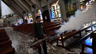 Un homme répand du répulsif contre le moustique  Aedes Aegyptidans une église de Caracas (Venezuela), le 5 février 2016. (CARLOS BECERRA / ANADOLU AGENCY / AFP)
