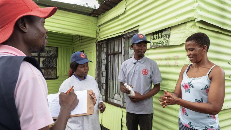 Une équipe de la Croix rouge internationale explique les gestes barrières contre le coronavirus à une habitante de Soweto, le 23 mars 2020 en Afrique du Sud. (LUCA SOLA / AFP)