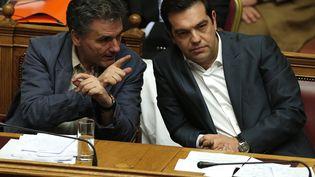 Le Premier ministre grec, Alexis Tsipras (à droite), et son ministre des Finances, Euclide Tsakalotos (à gauche), discutent lors d'une session au Parlement, le 25 juillet 2015 à Athènes. (ALKIS KONSTANTINIDIS / REUTERS)