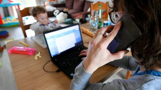 Une mère de famille pratique le télétravail. Photo d'illustration. (MAXPPP)