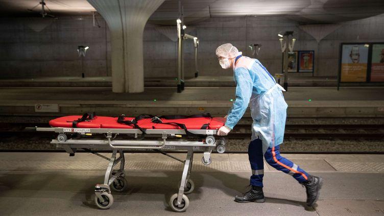 Un soignantprépare le brancard pourun patient atteint du Covid-19 dans un TGV médicalisé, en gare de Paris-Austerlitz, le 1er avril 2020. (THOMAS SAMSON / AFP)
