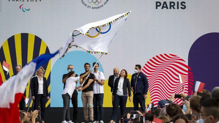 La maire de Paris Anne Hidalgo, le présidente du COJO Paris 2024 Tony Estanguet, la ministre des Sports Roxana Maracineanu, et la présidente du CNO France Brigitte Henriques avec le drapeau olympique des Jeux Olympiques, le 9 août 2021, à Paris. (AGENCE KMSP / AFP)