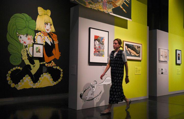 Une visiteuse passe devant l'œuvre Princess Jellyfish d'Higashimura Akiko (à gauche) durant une présentation à la presse de l'exposition Manga, au British Museum, à Londres, le 22 mai 2019 (DANIEL LEAL-OLIVAS / AFP)