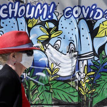 """Une femme marche devant une fresque murale où est écrit """"Atchoum ! Covid-19"""" dans les rues de Paris, le 20 avril 2020. (CHESNOT / GETTY IMAGES EUROPE)"""