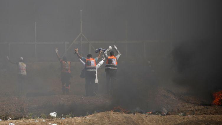 Des secouristes palestiniens approchent les mains en l'air de la frontière pour atteindre des manifestants blessés par les forces israéliennes, le 14 mai 2018. (THOMAS COEX / AFP)