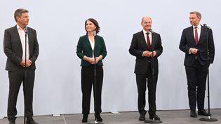 Robert Habeck et Annalena Baerbock, des Verts, le social-démocrate Olaf Scholz et le leader du parti libéral-démocrate, Christian Lindner, lors d'une déclaration sur un accord préliminaire entre les trois forces politiques pour la formation d'un gouvernement, le 15 octobre 2021 à Berlin (Allemagne). (CHRISTOF STACHE / AFP)