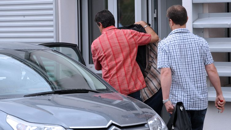 Des policiers sortent de la gendarmerie de Vielmur-sur-Agout (Tarn) pour transférer un homme s'accusant du meurtre de Patricia Bouchon vers Toulouse (Haute-Garonne), le 30 juin 2012. (ERIC CABANIS / AFP)