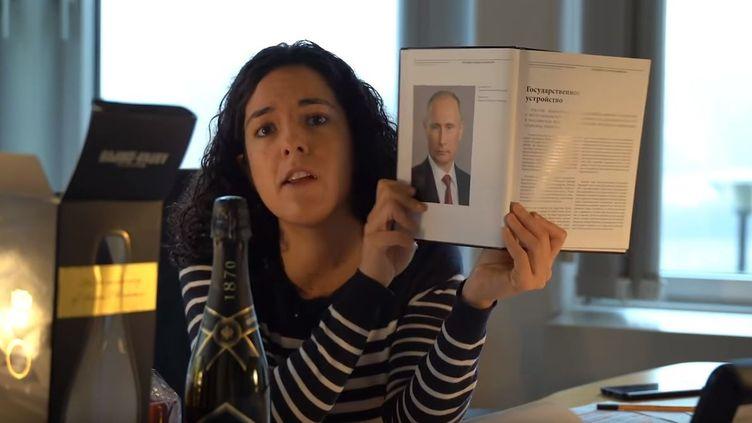"""La député européenne Manon Aubry montre la """"photo"""" et le """"champagne"""" offert par Vladimir Poutine aux députés européens. (CAPTURE D'ÉCRAN YOUTUBE)"""
