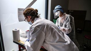 """Des employées d'un laboratoire médical participent à une campagne de dépistage organisée lors d'un """"drive-test' à Villefranche-sur-Saône (Rhône), le 3 avril 2020. (ANTOINE MERLET / HANS LUCAS / AFP)"""