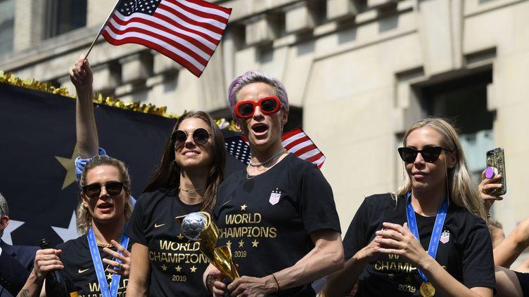 Megan Rapinoe, capitaine de l'équipe de football américaine, entourée d'autres joueuses, lors de leur célébration de championnes du monde le 10 juillet 2019 à New York (Etats-Unis). (JOHANNES EISELE / AFP)