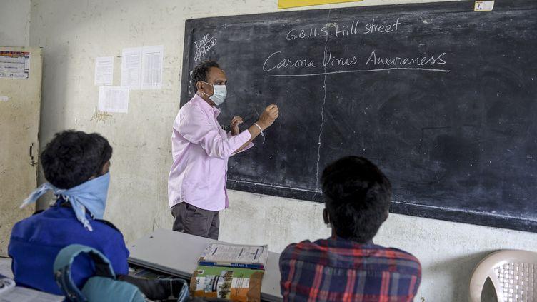 Un enseignant et deux de ses élèves dans un lycée de Secunderabad le 4 mars 2020 (NOAH SEELAM / AFP)