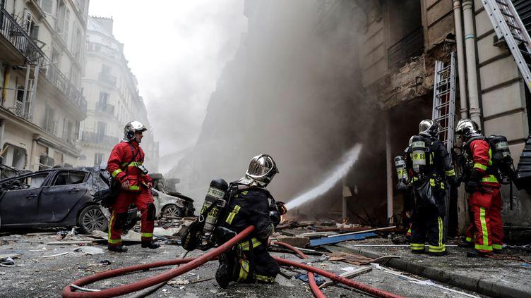 Les pompiers éteignent les flammes, rue de Trévise à Paris, après l'explosion, le 12 janvier 2019. (THOMAS SAMSON / AFP)