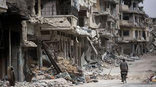 5 juin 2014, un homme à vélo adsn les rues dévastée de Homs, en Syrie. (DUSAN VRANIC / AP / SIPA)