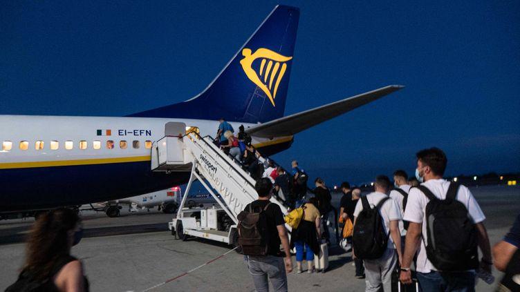 Des passagers embarquent dans un avion, sur la île de Crète, en Grèce, le 13 juin 2021. (NICOLAS ECONOMOU / NURPHOTO / AFP)