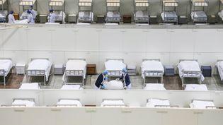 Des membres du personnel médical installent des lits pour accueillir des patients présentant des symptômes du nouveau coronavirus, le 5 février 2020 à Wuhan (Chine). (AFP)