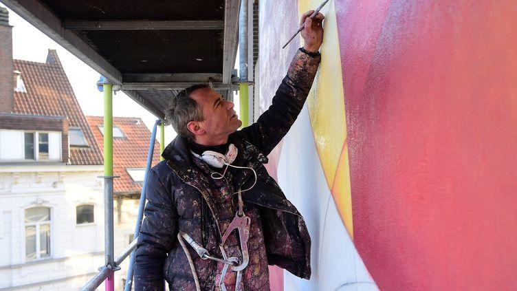 Guillaume Bottazzi brosse depuis un mois une peinture géante à Bruxelles, novembre 2016  (EMMANUEL DUNAND / AFP)