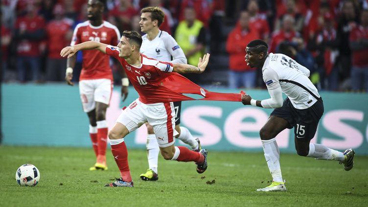Paul Pogba accroche Granit Xhaka, lors du match entre la France et la Suisse, le 19 juin 2016. (MUSTAFA YALCIN / ANADOLU AGENCY / AFP)