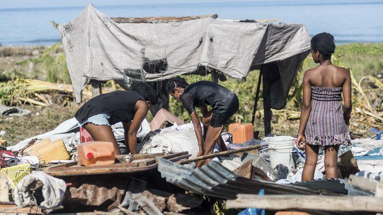 Des haïtiennes tentent de trouver des produits de valeur ou de première nécessité dans les ruines de leur maison, détruite par le séisme, samedi 14 août 2021 (REGINALD LOUISSAINT JR / AFP)