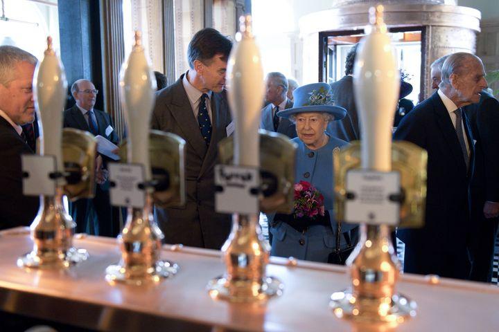 La reine Elizabeth II et le prince Philip (à droite), le 27 octobre 2016, dans un pub de Poundbury dans le sud-ouest de l'Angleterre. (JUSTIN TALLIS / AFP)