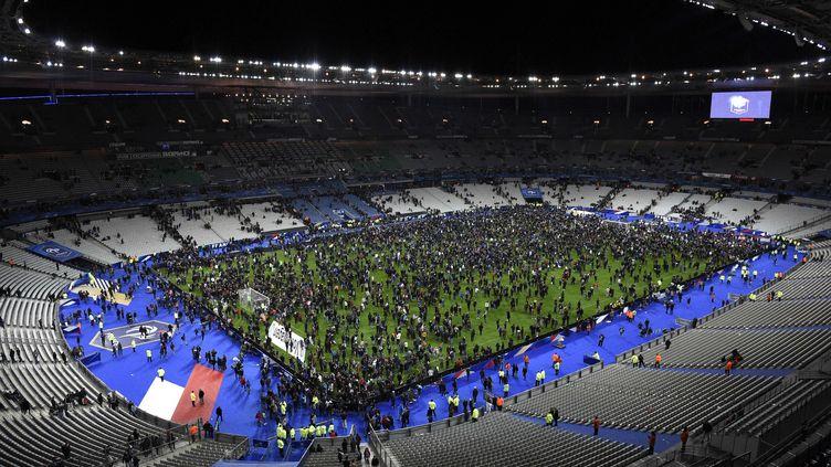 13 novembre 2015. 23h00. À la fin du match, le public du Stade de France est prié de rester en sécurité dans l'enceinte. La pelouse est alors envahie. (FRANCK FIFE / AFP)