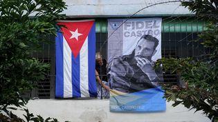 Une femme affiche un poster de Fidel Castro à La Havane après sa mort, le 28 novembre 2016. (YAMIL LAGE / AFP)