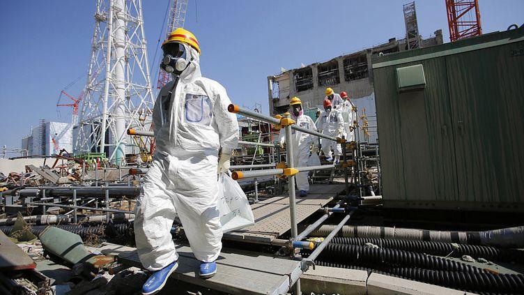 Des journalistes portant des combinaisons et des masques de protection sont escortés par les employés de TEPCO jusqu'au bâtiment commun de la piscine de combustible usé, alors qu'ils se rendent à la centrale nucléaire de Fukushima Daiichi, paralysée par le tsunami à Tokyo Electric Power Co. (TEPCO), dans la préfecture de Fukushima, le 6 mars 2013. (NOBORU HASHIMOTO / CORBIS NEWS / GETTY IMAGES)