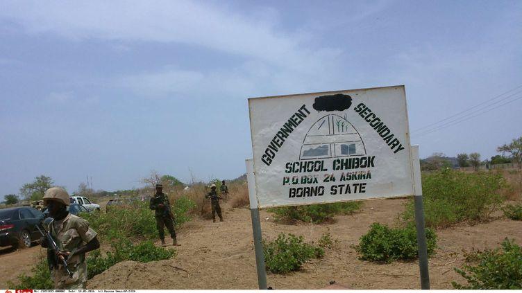 Des soldats aux côtés d'un panneau du lycée Chibok au Nigéria, le 21 avril 2014. (HARUNA UMAR/AP/SIPA)