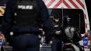Un policier contrôle un homme à scooter dans les rues de Paris,le 19 mars 2020, en pleine épidémie de Covid-19. (PHILIPPE LOPEZ / AFP)